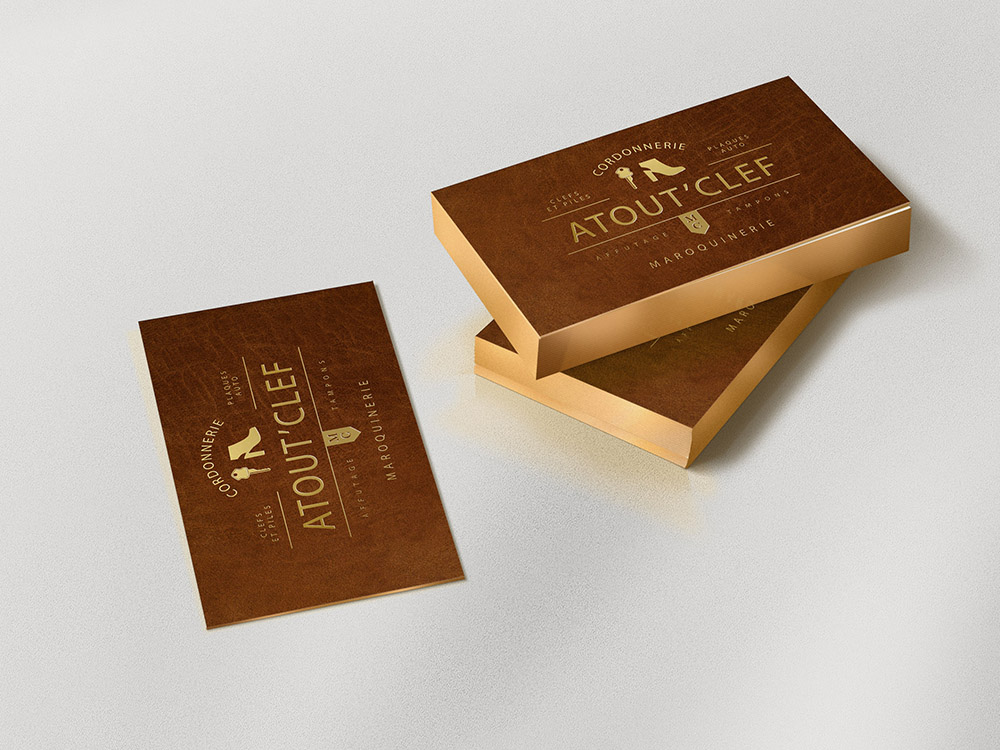 Trois paquet de carte de visites sont disposés sur une table. les cartes de visites présentent un fond texture cuir, avec le texte écrit en feuille d'or sur la carte. C'est en relief. Dessus est dessiné le logo de Atout Clef, une cordonnerie.