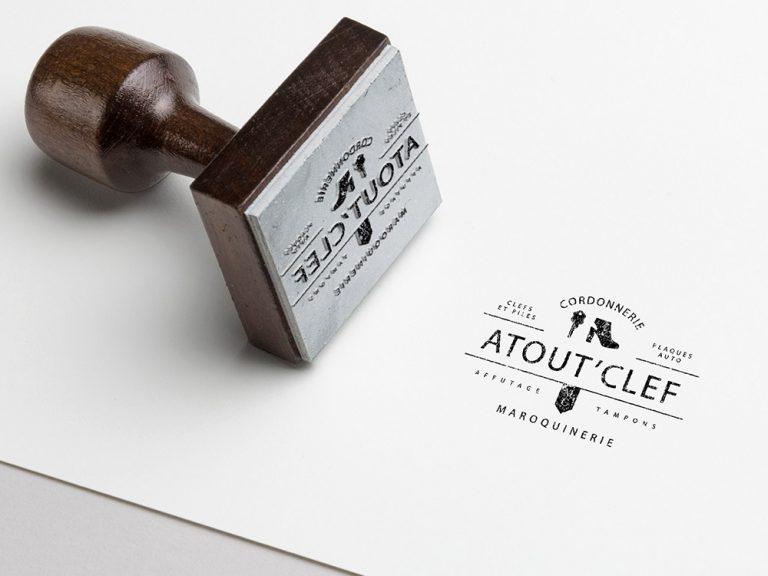 Tampon imprimant e logo atout clef. Logo composé d'une chaussure et d'une clef. Très minimaliste et épuré.