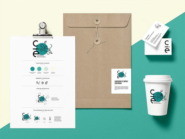 Mockup représentant toute l'identité visuelle de CIE. Une enveloppe, un format papier, carte de visite et goblet en carton. La charte est très coloré, dans les tons vert, bleu et jaune.